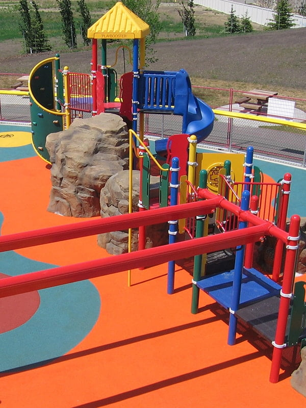 An installed playground project by PlayQuest that includes a playground structure with slides on a colourful rubber surface.