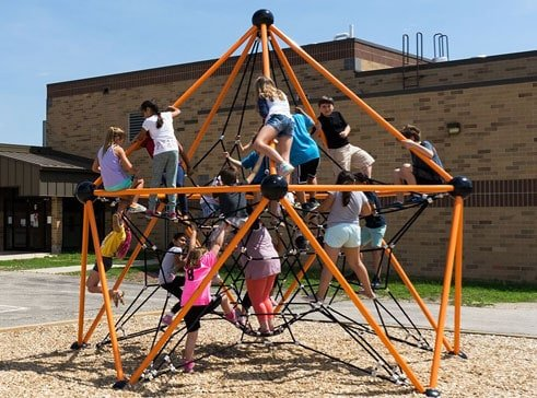 Kids enjoying a climbing structure on a school playground.
