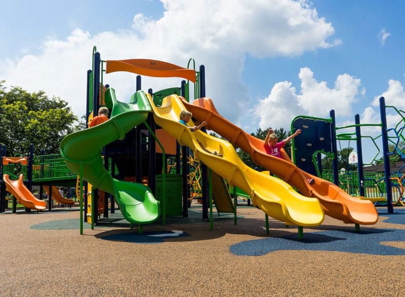 Commercial slides side by side incorporated into large playground equipment structure.