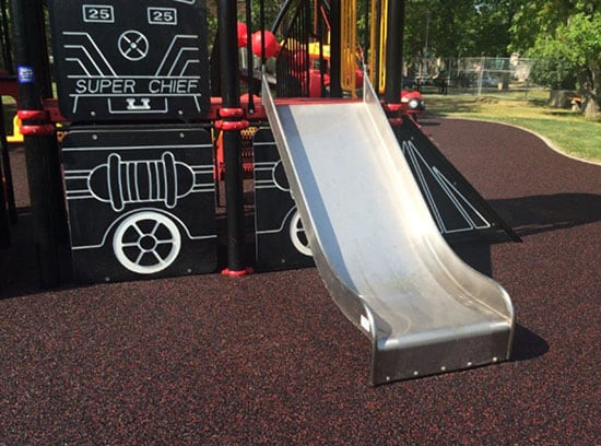 Red colour fleck added to rubber surfacing in a playground.