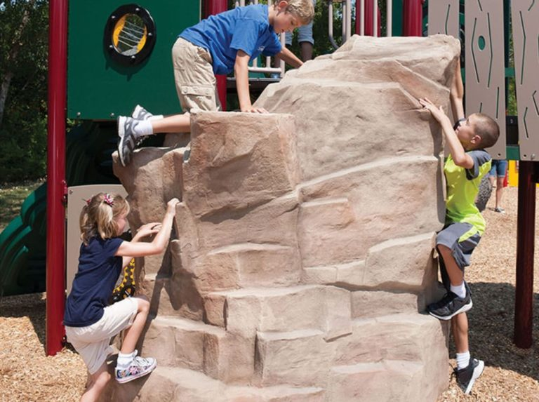 Kids climbing on playground equipment that looks like a large rock.
