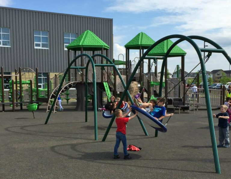 Kids enjoying new playground disc swings. Installed by PlayQuest at a school in Beaumont, Alberta.